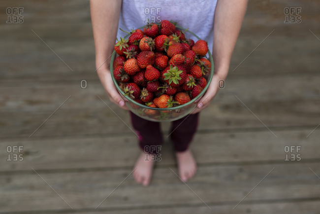 Low section of girl holding bowl in strawberries while standing on hardwood floor at home