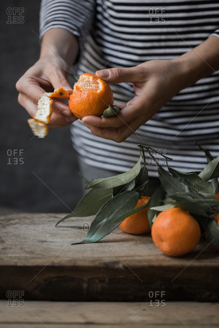 Woman Peeling Tangerine on the Table In Her Kitchen