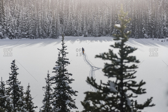 Two men skiing on frozen lake in the mountains above Duffey Lake