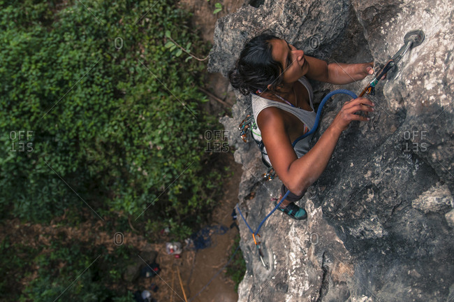Cat Ba Island, Vietnam - September 27, 2019: Woman clipping rope while rock climbing on limestone in Vietnam