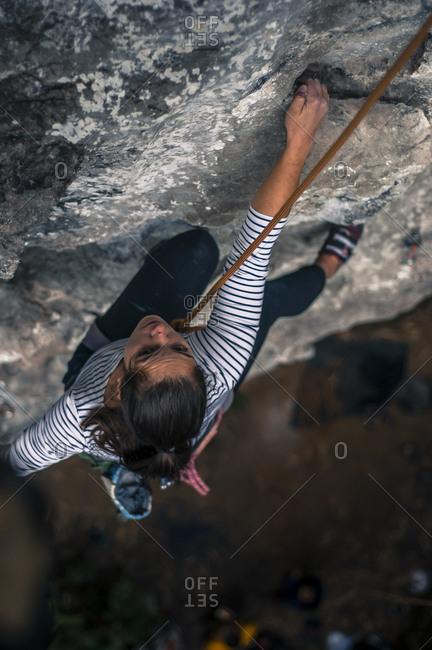 Young woman rock climbing on limestone in Vietnam, Cat Ba Island