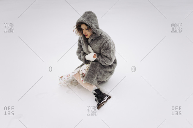 a woman in a fur coat sits on a snowy lake in winter