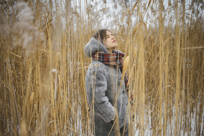 woman stands in the middle of high dry grass in winter