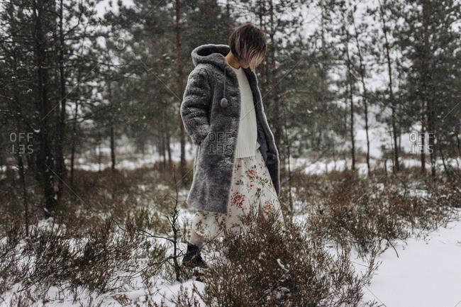A woman walks in the woods in winter