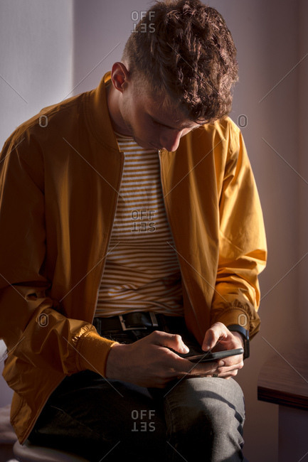 Young man focused on typing and sending messages on his mobile p