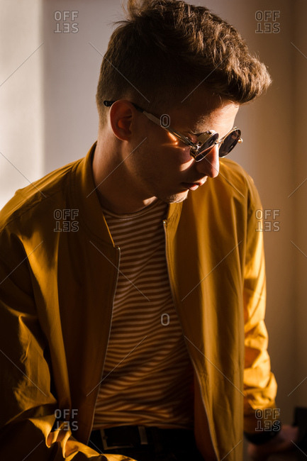Young man with round sunglasses and  sunshine is reflected on the lens