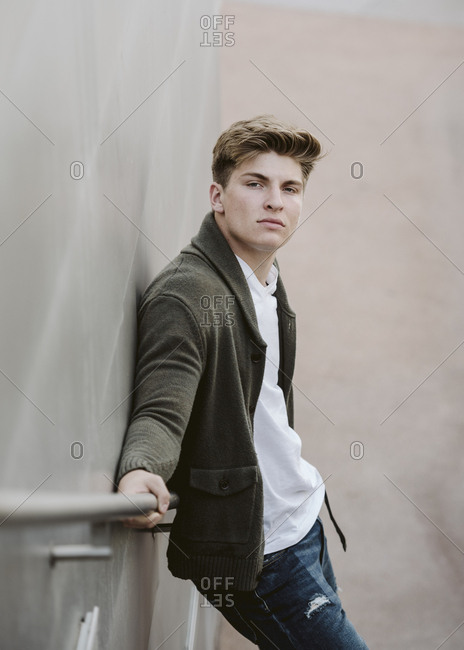 Handsome Man on Stairs leaning against railing