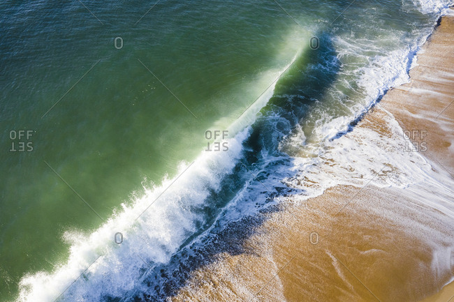 Shorebreak Wave crashing on the beach as seen by Aerial Drone