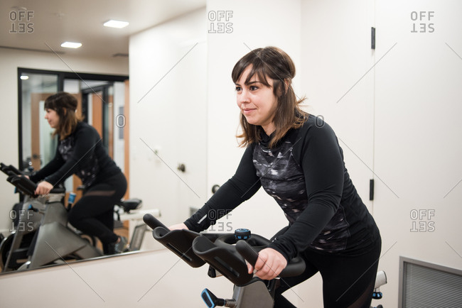 Woman in fitness room riding spin bike