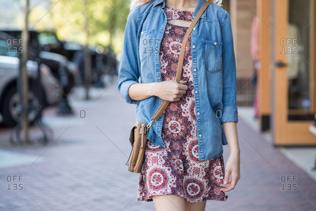 Tight frame of woman walking down street in dress holding purse