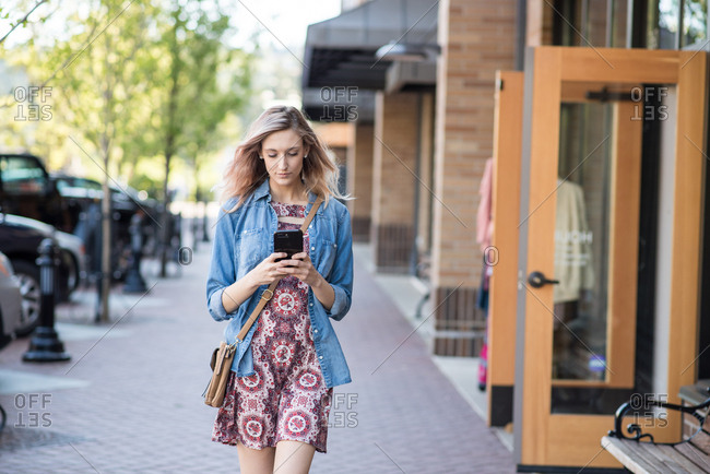 Woman texting on phone while walking down street