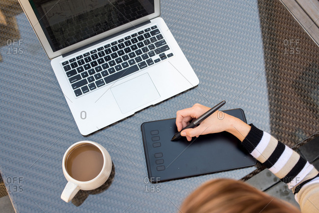 Top down photo of woman using drawing tablet with laptop