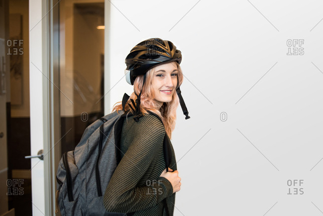 Young woman wearing bike helmet with backpack looking at camera