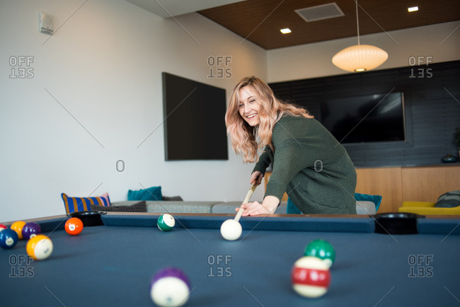 Woman smiling and lining up her pool shot