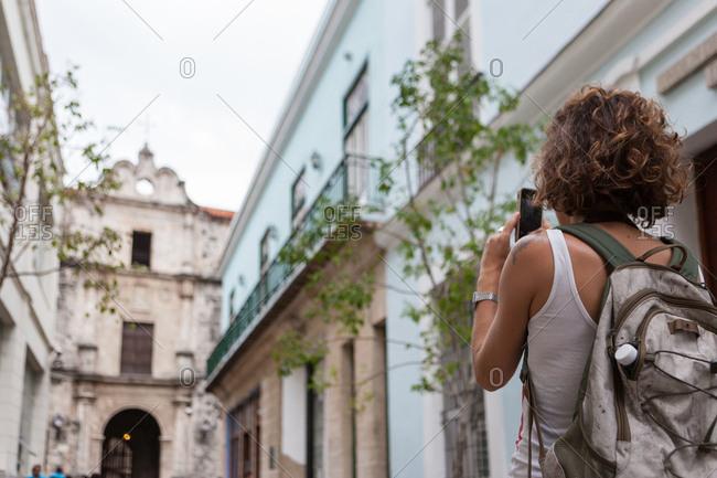 Western girl taking photo with smartphone in old Havana, Cuba