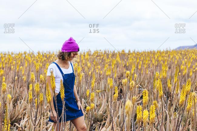 Girl with sunglasses walking in aloe vera field, Fuerteventura