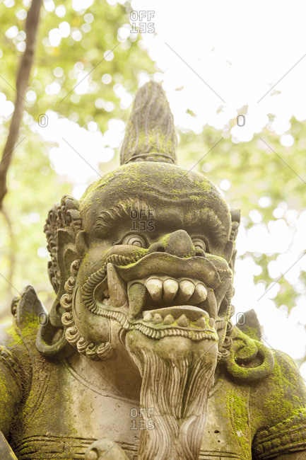 Stone carved demon Balinese statue with trees in the background, UBUD