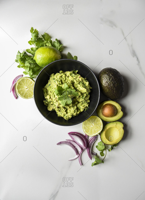 Bowl of guacamole surrounded by it's ingredients on a marble counter.