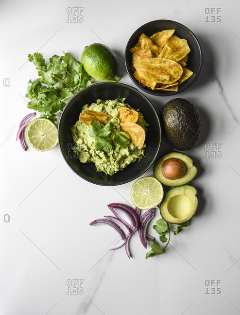 Bowl of guacamole and chips with it's ingredients on a marble counter.
