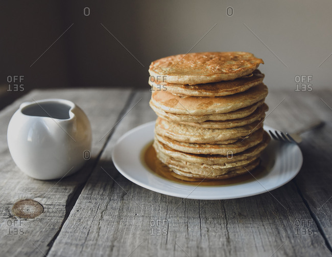 Close up of stack of pancakes with fork and  small jug of maple syrup.
