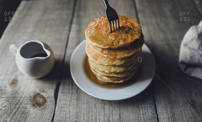 Stack of pancakes with fork stuck in them and jug of maple syrup.
