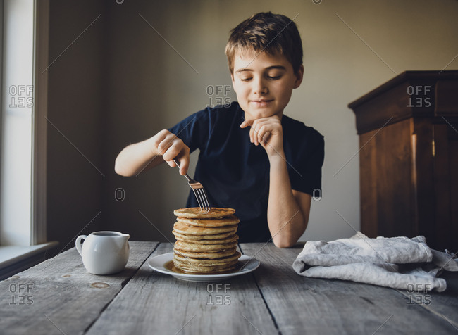Boy looking at a big stack of pancakes as he is about to eat them.