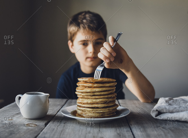 Close up of a boy sticking a fork into a big stack of pancakes.