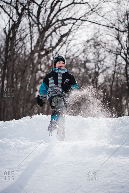 Young boy kicking snow in air on a winter day in wooded area.