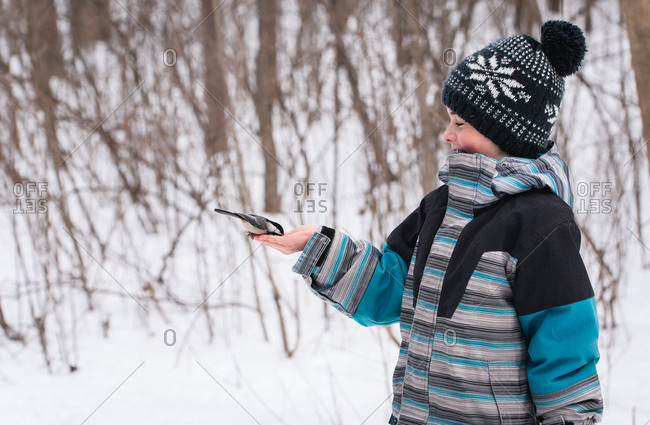 Boy happily feeding bird from his hand in wooded area on a winter day.