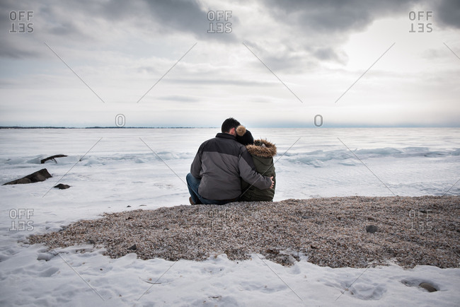Couple sitting together on icy lake shore on a cloudy winter day.