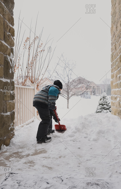 Young boy shoveling snow off of front steps during a snowstorm.