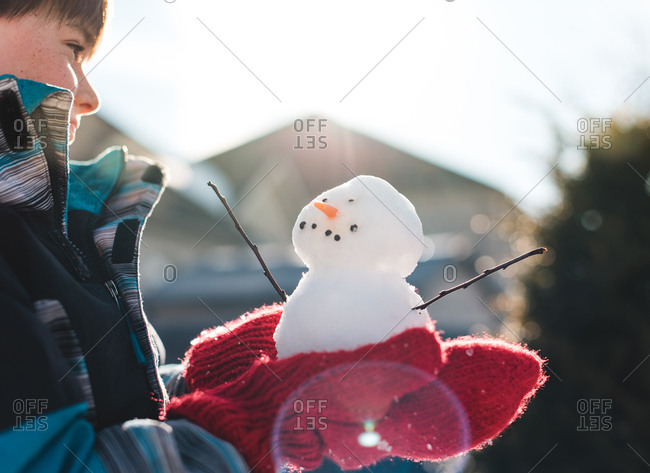 Young boy wearing red wool mittens holding a small snowman in the sun.