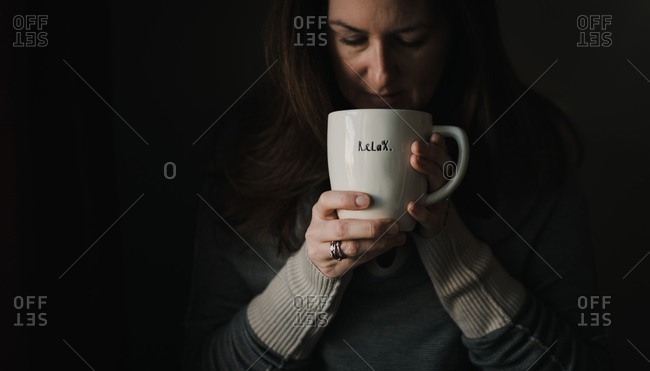 Woman drinking from large coffee mug with word relax written on it.