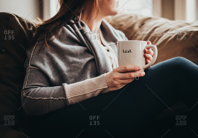Cropped image of woman holding mug with word relax on it on a couch.