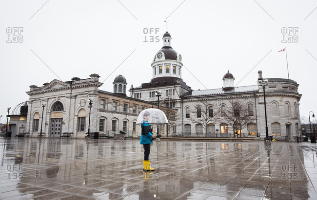 Small boy wearing rain gear holding umbrella in a rainy city square.