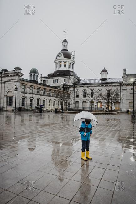 Boy in yellow rain boots holding umbrella in the rain in city square.