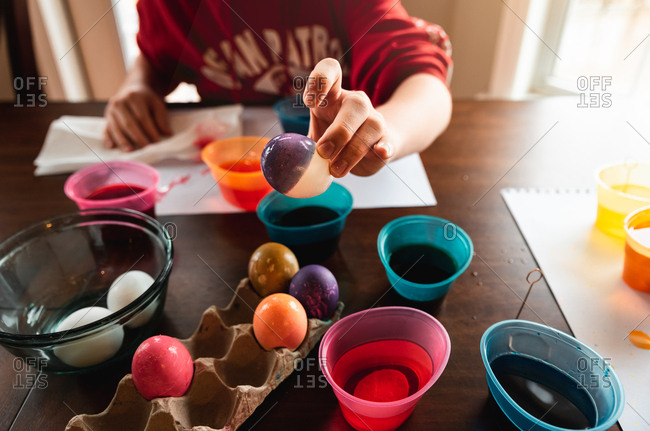 Crop of hand holding colored Easter egg with dye containers in back.
