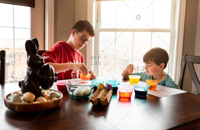 Two boys coloring Easter eggs with containers of dye at wooden table.