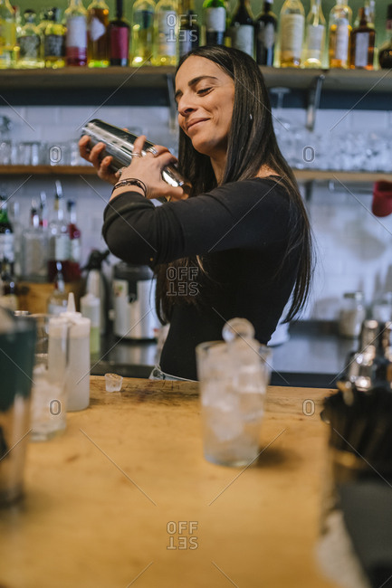 Young barwoman prepares an alcoholic cocktail in the bar