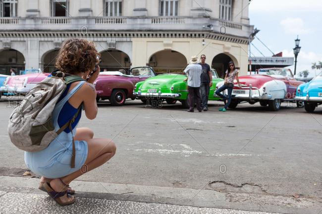 La Havana, Cuba - September 27, 2019: Western girl taking photo with film camera of vintage car Cuba