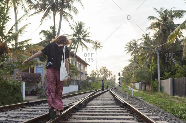 Ahanghama, Sri Lanka - February 15, 2019: Caucasian girl walking on train tracks Sri Lanka
