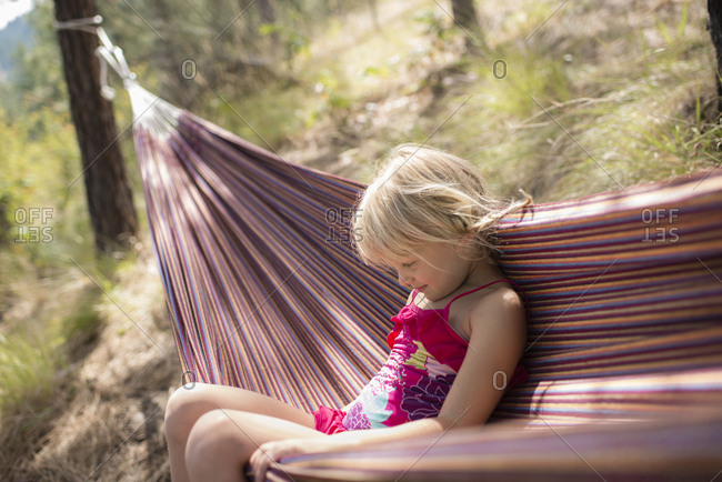 Girl sitting in hammock at forest