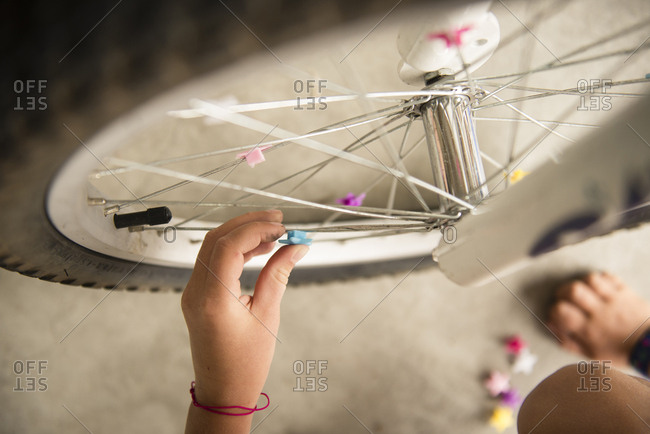 Cropped image of girl decorating bicycle tire