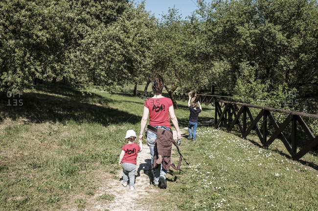 Mother walking in a mountain path with two children