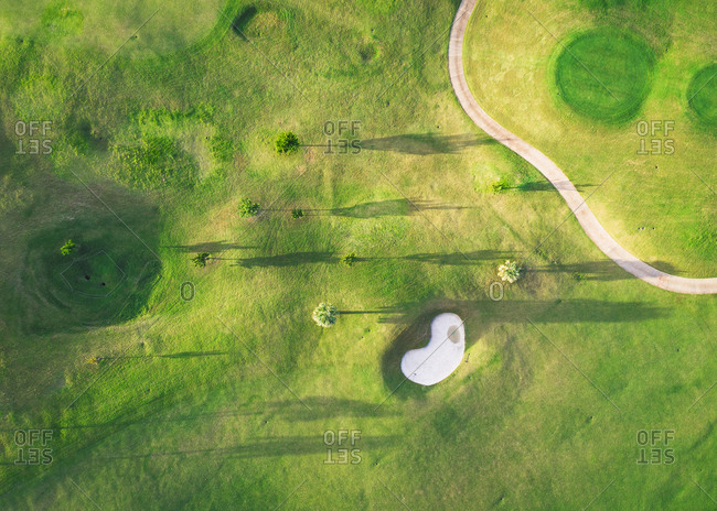 A golf course with trees and shadows from above