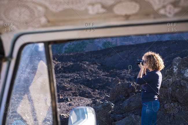Woman photographing with camera seen through travel trailer's window