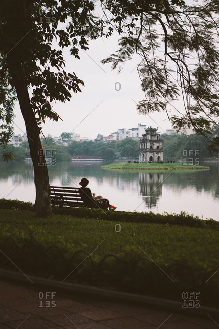 Rear view of woman looking at view while sitting on bench at Hoan Kiem Lake