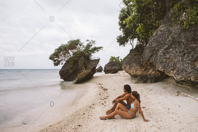 Side view of couple looking at view while sitting against rocks on shore