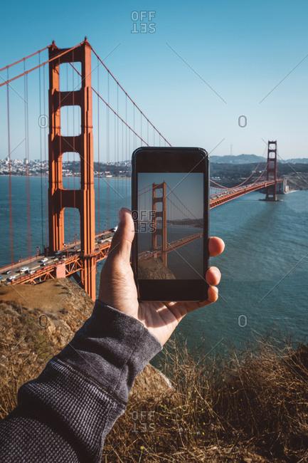 Tourist taking a photo of the golden gate bridge in San Francisco