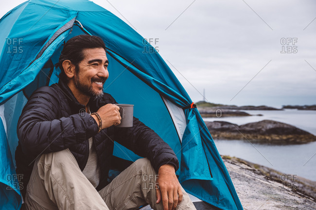 Man smiling holding a mug sitting at a camping tent by the sea